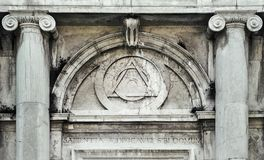 Eye of Providence, inside triangle interlaced with circle above doorway of building in Venice, Italy. It represents the eye of God watching over humanity, or Royalty Free Stock Photo