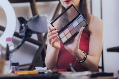 Beautiful woman with beige nail art holding eye shades palette. Eye shades palette. Beautiful charming woman with beige nail art holding eye shades palette stock images