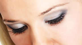 Eye shadow. Close female eye with silver-gray cosmetic make-up royalty free stock photos