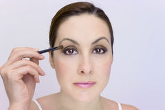 Eye shadow as part of cosmetics. A beautiful young woman uses eye shadow, photography Stock Images
