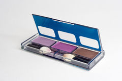 Eye shadow box. 3 color eye shadow in a open blue rectangle box with 2 brushes inside Royalty Free Stock Photo