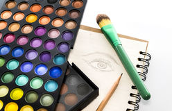Eye shadow color palette with brush and drawing eye on paper. Eye shadow color palette with brush and pencil and drawing eye on paper Stock Photo