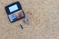 Eye shadow fell and scattered on carpet. Top view. Eye shadow fell and scattered on carpet royalty free stock image