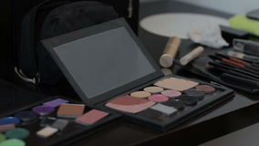 Eye shadow Makeup applied with a Brush. On the table is scattered around various cosmetics stock video