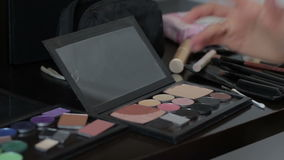 Eye shadow Makeup applied with a Finger. On the table is scattered around various cosmetics stock video footage