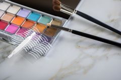 Eye shadow palette, brushes and artificial eyelid crease double tapes for eye makeup on marble beauty desk table. Eye shadow palette, brushes and artificial stock photo