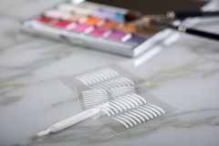 Eye shadow palette, brushes and artificial eyelid crease double tapes for eye makeup on marble beauty. Eye shadow palette, brushes and artificial eyelid crease stock photo