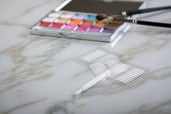 Eye shadow palette, brushes and artificial eyelid crease double tapes for eye makeup on marble beauty. Eye shadow palette, brushes and artificial eyelid crease stock photos
