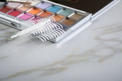 Eye shadow palette, brushes and artificial eyelid crease double tapes for eye makeup on marble beauty desk table. Eye shadow palette, brushes and artificial stock images