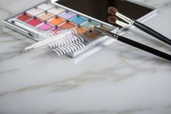 Eye shadow palette, brushes and artificial eyelid crease double tapes for eye makeup on marble beauty desk table stock photo