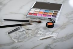 Eye shadow palette, brushes, fake lashes, tweezers and artificial eyelid crease double tapes for eye makeup on marble beauty desk. Eye shadow palette, brushes stock photography