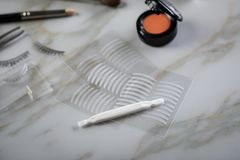 Eye shadow palette, brushes, fake lashes, tweezers and artificial eyelid crease double tapes for eye makeup on marble beauty desk. Eye shadow palette, brushes royalty free stock photography