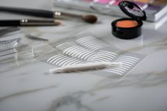 Eye shadow palette, brushes, fake lashes, tweezers and artificial eyelid crease double tapes for eye makeup on marble beauty desk. Eye shadow palette, brushes royalty free stock photos