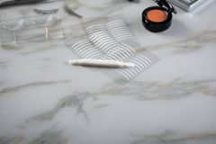 Eye shadow palette, brushes, fake lashes, tweezers and artificial eyelid crease double tapes for eye makeup on marble beauty desk. Table royalty free stock photo