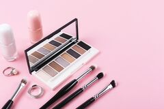 Eye shadow palette and makeup accessories on pastel pink background