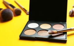 Eye shadow palette with professional makeup brush. On yellow background royalty free stock photography