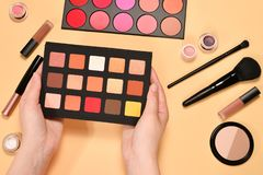 Eye shadow palette on woman hand. Professional makeup products with cosmetic beauty products, foundation, lipstick,  eye shadows,. Brushes and tools. Top view stock image