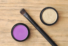 Eye shadows in black boxes and brush on wood table Stock Images