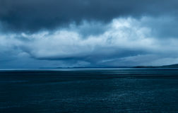 Eye shaped storm at dusk near Mull, Scotland. Gathering storm at dusk over an empty sea near Mull, Oban and Lismore, in the Inner Hebrides of Scotland. The royalty free stock images
