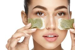 Eye Skin Beauty. Young Woman With Natural Facial Makeup. Holding Green Tea Bags On White Background. High Resolution Royalty Free Stock Image