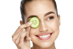 Eye Skin Care. Woman With Natural Makeup Using Cucumber. As Eye Remedy For Removing Dark Circles. High Resolution royalty free stock photography