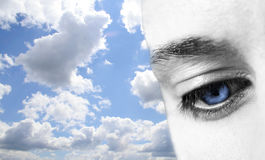 Eye in the sky. The blue eye of a man in front of sky Stock Image