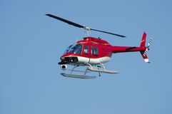 Eye in the sky. A bright red Bell 206 Jet Ranger helicopter with a camera on a Fleet Week Air Show in 2006. A little motion blur on rotor blades Royalty Free Stock Image