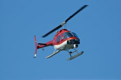 Eye in the sky 3. A bright red helicopter with a camera. A little motion blur on rotor blades Stock Images