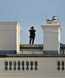 Eye in the Sky. A U.S. Secret Service Agent standing on the roof of The White House using powerful binoculars for security surveillance. (Washington D.C stock photos