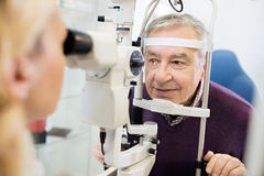 Eye specialist determines distance of eyes pupil to patient Stock Photos