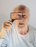 Eye spy. The senior spys with one eye through a magnifying glass Stock Photography