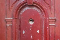 Eye spy through the looking hole. Eye spy through the looking round hole in the old red wooden door Stock Photo