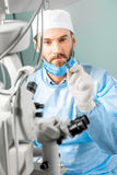 Eye surgeon with surgical scissors. Eye surgeon holding small surgical scissors for eye operation in the operating room near the microscope Royalty Free Stock Image