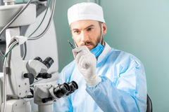 Eye surgeon with surgical scissors. Eye surgeon holding small surgical scissors for eye operation in the operating room near the microscope. Image with small Royalty Free Stock Photography