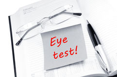 Eye test. Appointment reminder with glasses on open diary Royalty Free Stock Photo