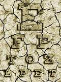 Eye test chart on the cracked earth. Stock Images