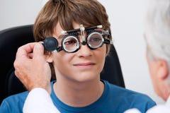 Eye Test Through Trial Frames. Optometrist taking eye test through trial frames at the clinic royalty free stock photo