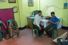 Eye testing camp. KOLKATA , INDIA - MARCH 19, 2017 : Male Doctor eye specialist checking eye sight of adult male sitting on a chair, at a free public eye testing Royalty Free Stock Images