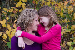 Eye to Eye. A happy fall portrait of a mother and her pre-teen daughter Royalty Free Stock Photography
