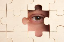 Eye watching through puzzles Royalty Free Stock Images