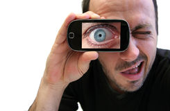 Eye zooming. Closeup of a man looking in his cell phone Royalty Free Stock Images