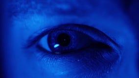 Eyeball a dilatação dos alunos, próxima acima do olho iluminado com luz azul na obscuridade filme