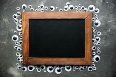 Eyeball frame with blank chalkboard for text. Halloween background Royalty Free Stock Photo