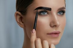 Eyebrow coloring. Woman applying brow tint with makeup brush. Closeup. Girl model using liquid peel-off brow gel, beauty product on eyebrows royalty free stock photography