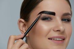 Eyebrow coloring. Woman applying brow tint with makeup brush. Closeup. Girl model using liquid peel-off brow gel, beauty product on eyebrows royalty free stock photo