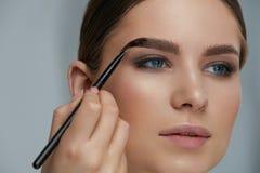 Eyebrow coloring. Woman applying brow tint with makeup brush. Closeup. Girl model using liquid peel-off brow gel, beauty product on eyebrows stock photography