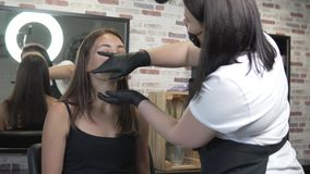 Eyebrow correction in a beauty salon. Master prepares the skin for waxing extra hair. Eyebrow shaping stock video