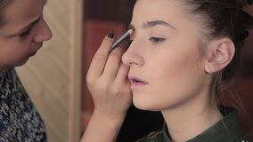 Eyebrow makeup for model in preparation for photography stock footage