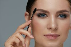 Free Eyebrow Makeup. Woman Brushing Brows With Gel Brush Closeup Stock Image - 150988331