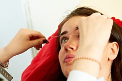 Eyebrow thread correction. Stylist making eyebrow thread correction on face of beautiful girl Royalty Free Stock Image